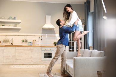 Lovely young interracial couple dancing at home. Space for text
