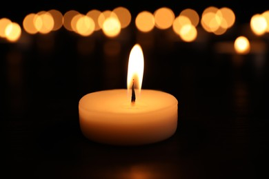 Burning candle on dark surface. Memory day
