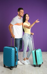 Happy couple with suitcases for summer trip near purple wall. Vacation travel