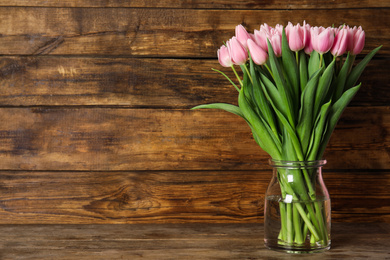 Beautiful pink spring tulips in vase on wooden table. Space for text