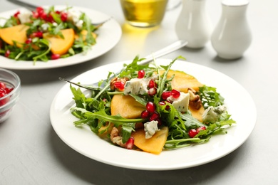 Delicious persimmon salad with pomegranate and arugula served on light grey table
