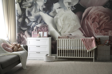 Baby room interior with stylish crib and floral wallpaper