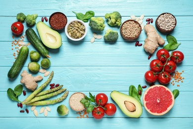 Frame of fresh vegetables, fruits and seeds on light blue wooden table, flat lay. Space for text