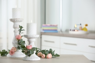 Vintage candlesticks with burning candles, roses and eucalyptus on table in room. Space for text