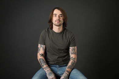 Young man with tattoos on arms against black background