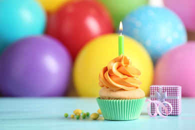 Delicious birthday cupcake with burning candle and gift on light blue wooden table. Space for text