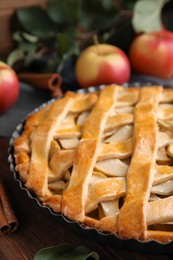 Delicious traditional apple pie on wooden table, closeup