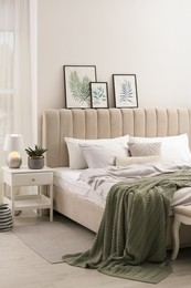 Bed with stylish grey linens near white wall in room