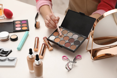 Beauty blogger with brush and eyeshadow palette at table, closeup