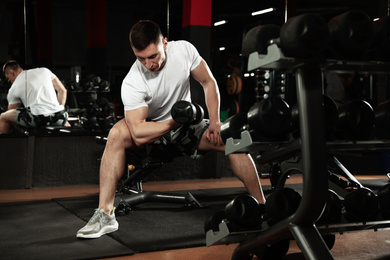 Man working out with dumbbell in modern gym