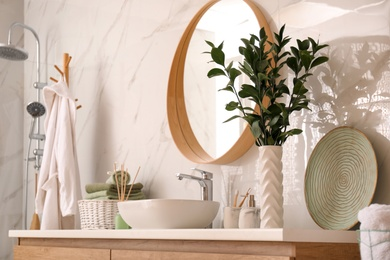 Vase with beautiful branches and toiletries near vessel sink in bathroom. Interior design