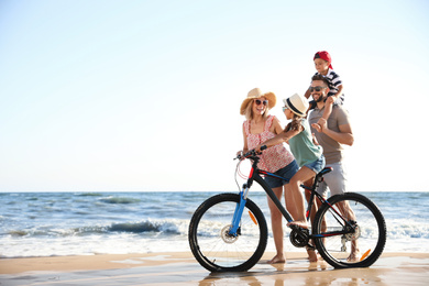 Happy family with bicycle on sandy beach near sea