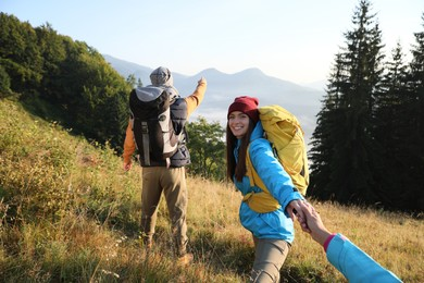 Tourists with backpacks hiking in mountains on sunny day