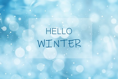 Phrase Hello Winter and snowfall on light blue background, bokeh effect