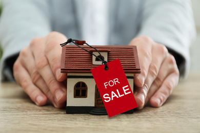 Real estate agent holding house model with SALE label at wooden table, closeup