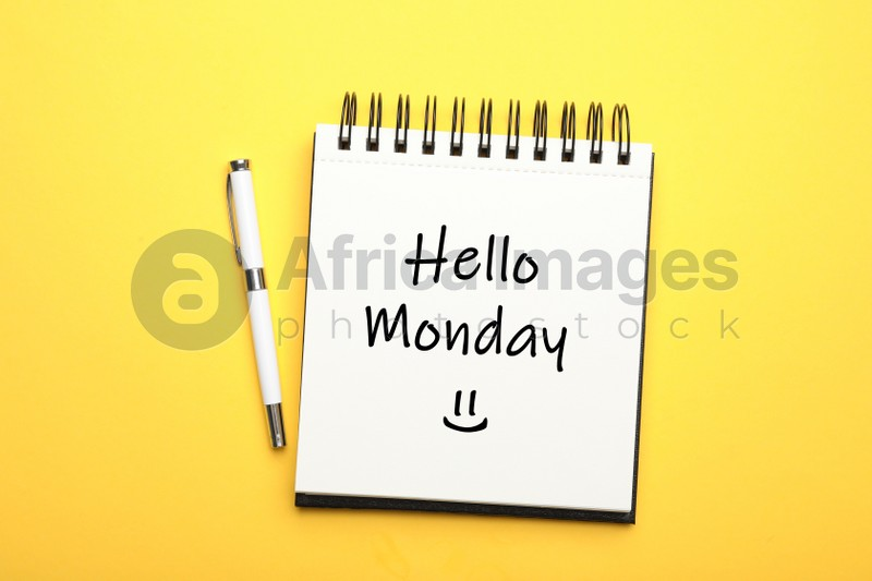 Start your week with good mood. Open notebook with text Hello Monday and pen on yellow background, flat lay