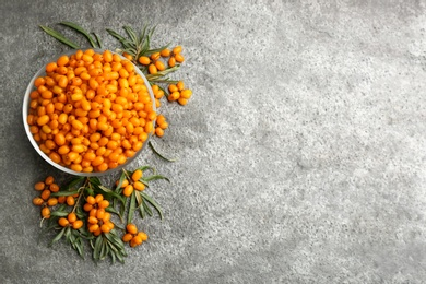 Fresh ripe sea buckthorn on grey table, flat lay. Space for text