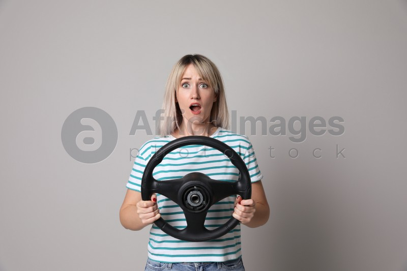 Emotional woman with steering wheel on grey background