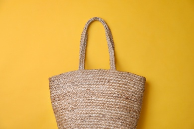 Stylish straw bag on yellow background, top view. Summer accessory