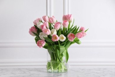 Beautiful bouquet of tulips in glass vase on white marble table