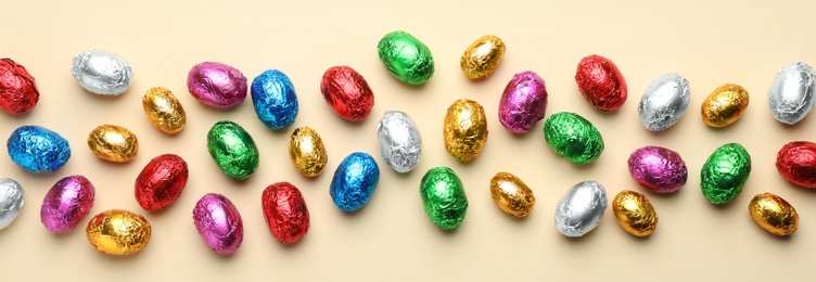 Chocolate eggs wrapped in colorful foil on beige background, flat lay. Banner design