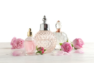 Different perfume bottles and flowers on light background