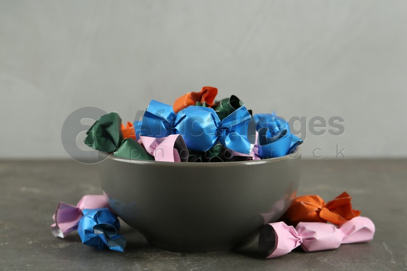 Candies in colorful wrappers on grey table