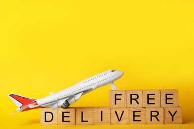 Toy plane and cubes with words FREE DELIVERY on yellow background. Logistics and wholesale concept