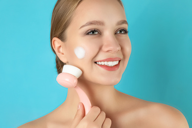 Young woman washing face with brush and cleansing foam on light blue background. Cosmetic products