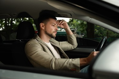 Stressed businessman in driver's seat of modern car