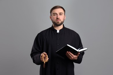 Priest with beads and Bible praying on grey background