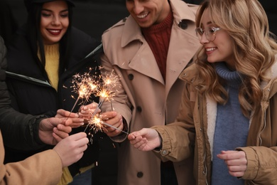 People in warm clothes holding burning sparklers on dark background
