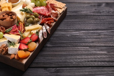 Assorted appetizers served on black wooden table. Space for text