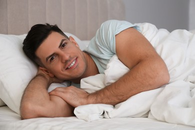 Man lying in bed with white linens at home