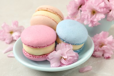 Delicious colorful macarons and pink flowers on light grey table, closeup