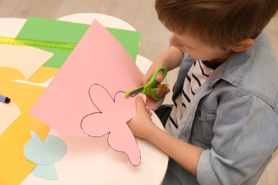 Little boy cutting color paper with scissors at table indoors