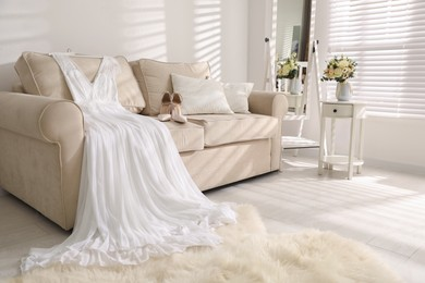 Beautiful wedding dress and shoes on sofa indoors