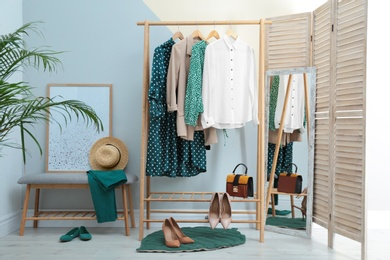 Wardrobe rack with women's clothes and shoes at color wall in room