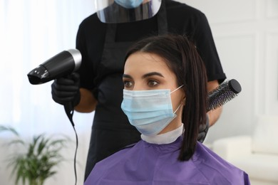 Professional stylist working with client in salon, closeup. Hairdressing services during Coronavirus quarantine