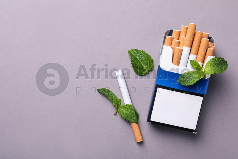 Pack of menthol cigarettes and mint leaves on grey background, flat lay. Space for text