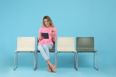 Young woman with tablet waiting for job interview on light blue background