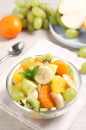 Delicious fresh fruit salad in bowl on table