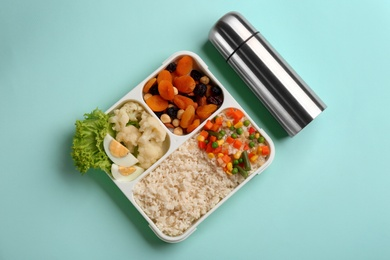 Thermos and lunch box with food on turquoise background, flat lay