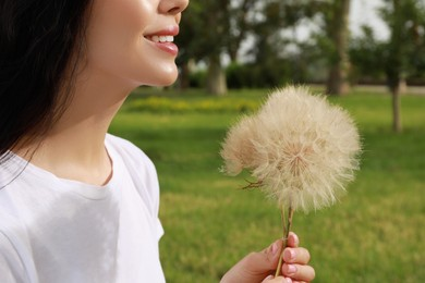 Beautiful young woman with large dandelions in park, closeup. Allergy free concept