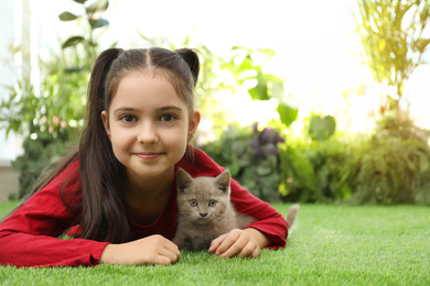 Girl with Scottish straight baby cat on green grass