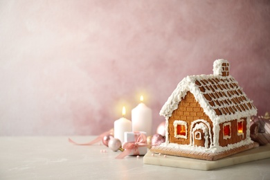 Beautiful gingerbread house decorated with icing on light table, space for text