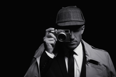 Old fashioned detective with camera on dark background, black and white effect