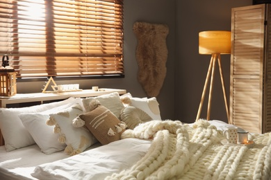 Bed with cozy knitted blanket and cushions near window in room. Interior design