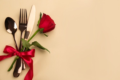 Beautiful cutlery set, flower and red bow on beige background, flat lay with space for text. Valentine's Day dinner