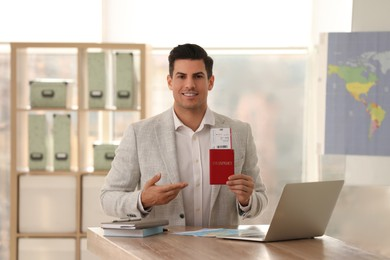Travel agent with ticket and passport in office
